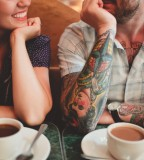 tattooed couple having coffee
