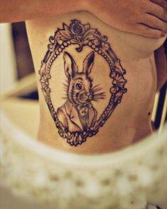 Alice in wonderland rabbit tattoo on arm