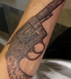 Black ornaments and gun tattoo