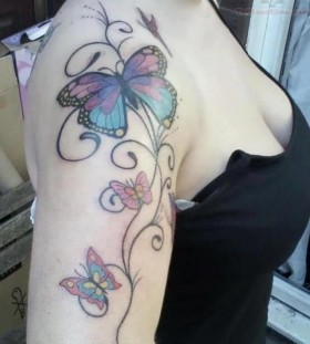 Black shoulder butterfly tattoo on arm