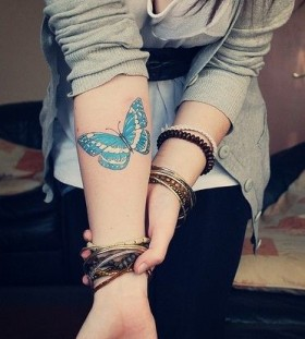 Blue simple butterfly tattoo on arm
