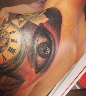 Old watch and eye tattoo on shoulder