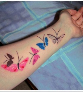 Pink and blue butterfly tattoo on arm