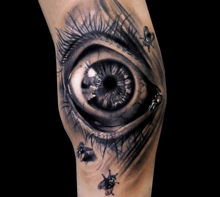 small insect and scary eye tattoo on arm tattoomagz