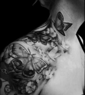 Women black and white shoulder butterfly tattoo on arm
