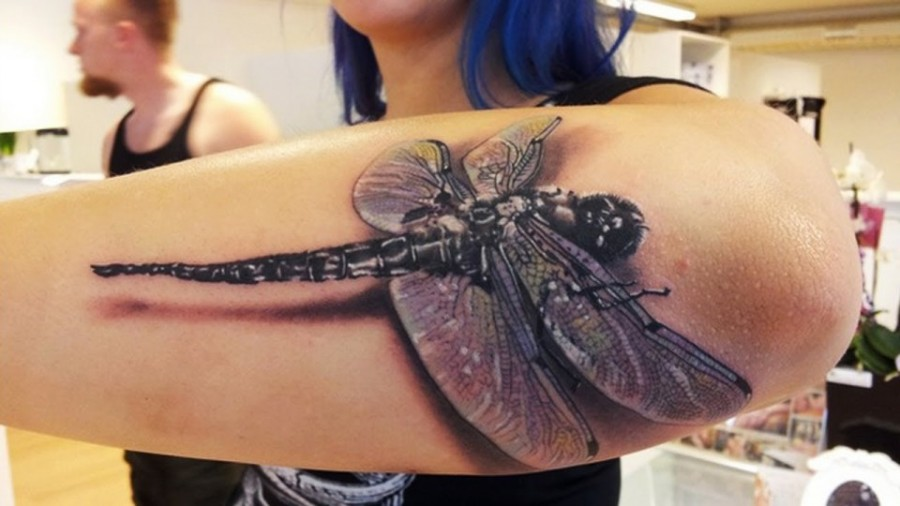 3D dragonfly on arm tattoo