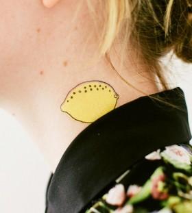 Girl with lemon tattoo on neck