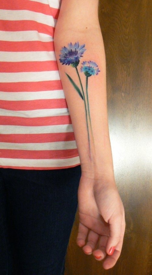 blue flower tattoo on arm