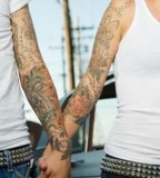 Tattooed Hispanic Couple Holding Hands