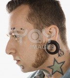 Man With Neck Tattoos And Ear Piercings