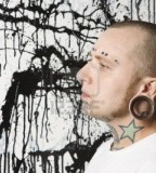 Tattooed And Pierced Man Against Paint Splattered Background