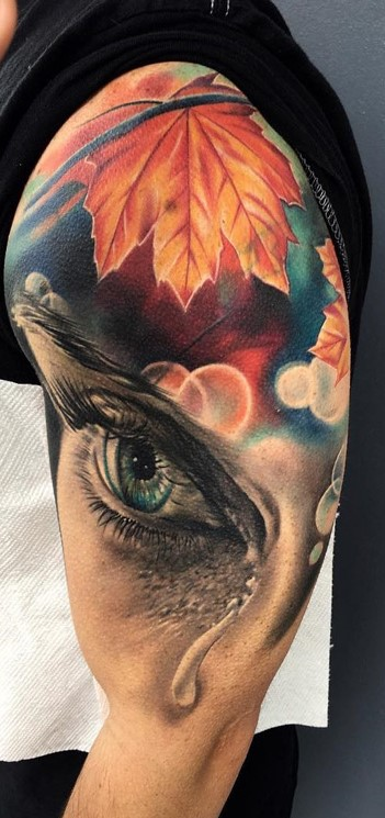 teardrop-on-eye-with-autumn-leaves-background-tattoo