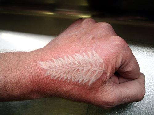 white ink tattoo leaf