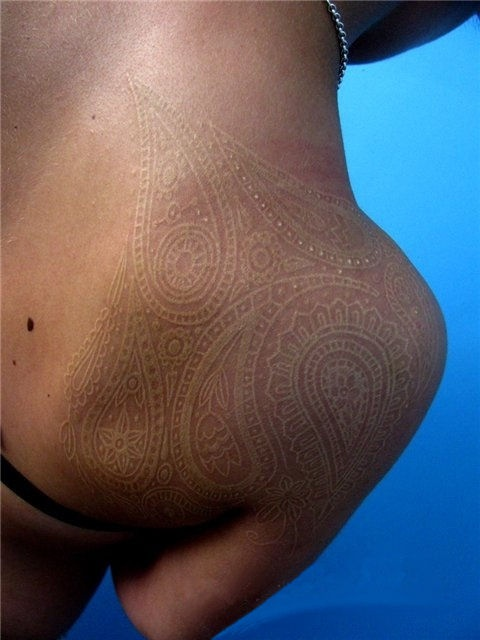 white ink tattoo on a shoulder