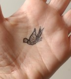 elegant bird tattoo on hand
