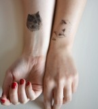 black and white cats tattoo on arms