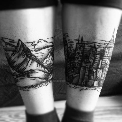 leg tattoo mountains and city
