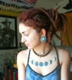 tattooed girl with dreadlocks blue moon phases on chest
