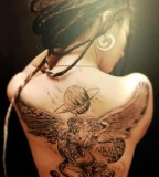 tattooed girl with dreadlocks devil and angel back tattoo