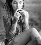 tattooed girl with dreadlocks eating on grass