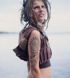 tattooed girl with dreadlocks near water