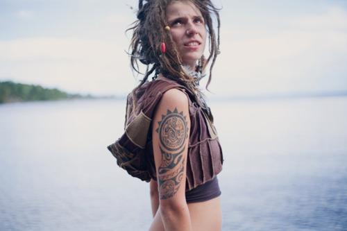 tattooed girl with dreadlocks near water