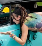 tattooed girl with dreadlocks rainbow wings blue car