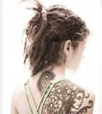 tattooed girl with dreadlocks shoulder tattoo flowers face
