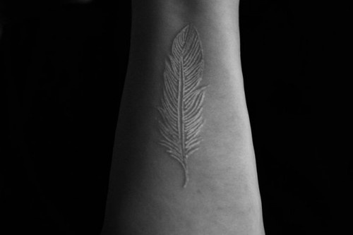 wrist tattoo white ink feather