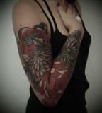 black and red flower arm sleeve tattoo by guy le tattooer