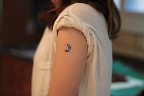 tiny boat tattoo on arm