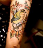 Colorful flying bird tattoo