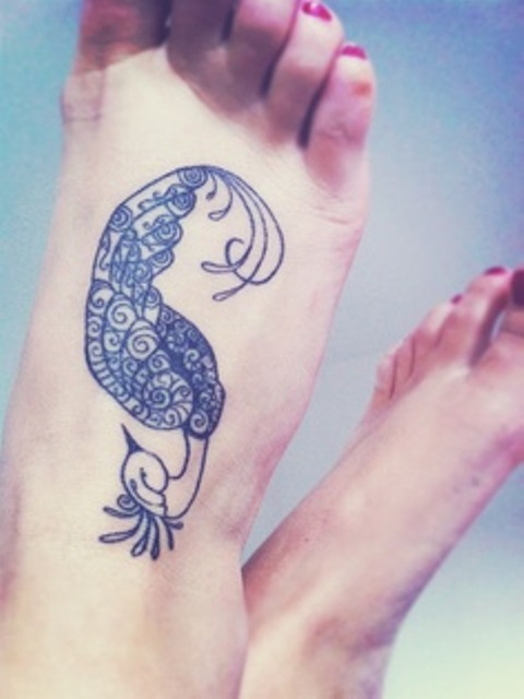 blue ink tattoo peacock on foot