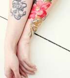 girly tattoo anchor and flowers on arms