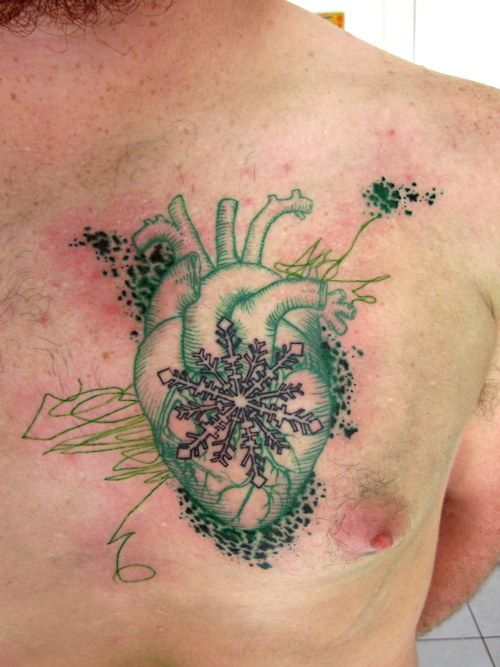 green tattoo heart with snowflake on chest