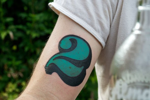 typographic tattoo green  number on arm