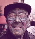 Colorful tattoos on old men face