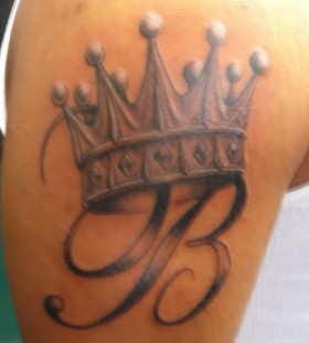 Letter and crown tattoo