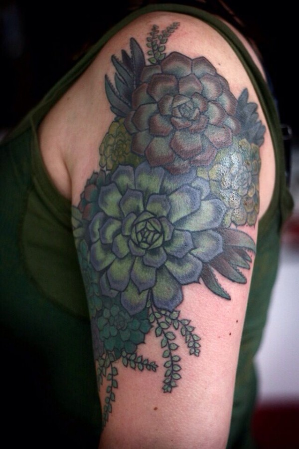 alice carrier tattoo blue and green coloured flowers on upper arm