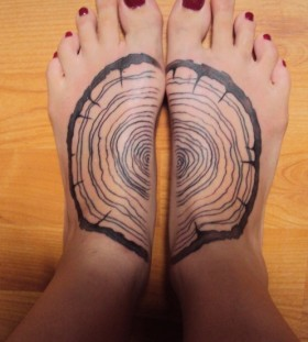black ink wood tattoo on feet