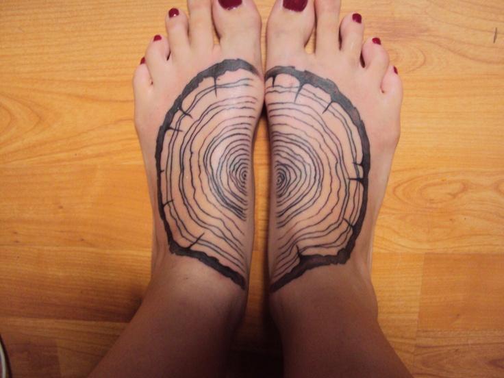 black ink wood tattoo on feet