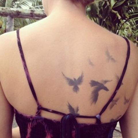 modern tattoo subtle birds on back
