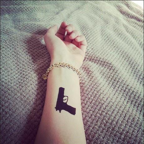 Black arm guns tattoo
