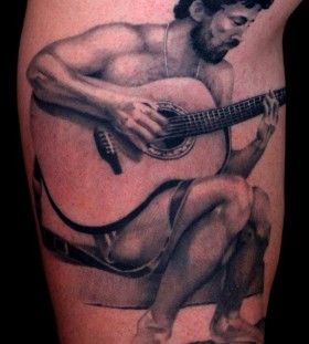 Man and guitar tattoo by Art Junkies