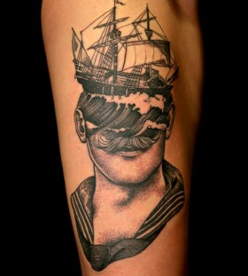 Ship and man head tattoo