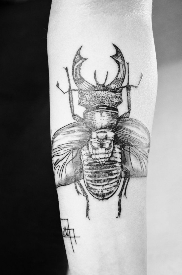 Black insect tattoo