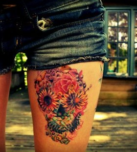 Adorable flowers and skull tattoo on leg