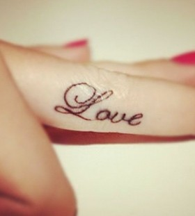 Amazing red nails and love tattoo on arm