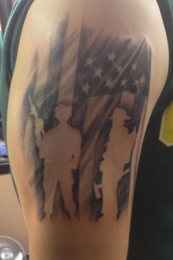 American flag style soldier tattoo on arm