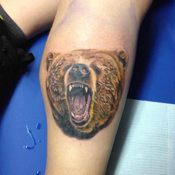 Angry brown bear tattoo on leg
